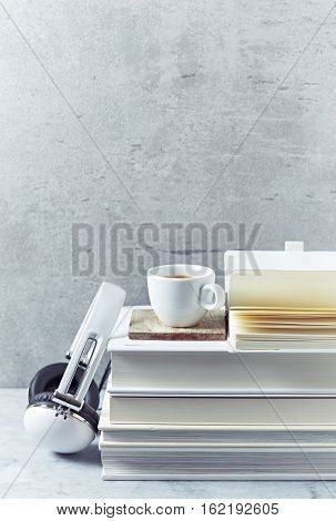 A cup of coffee on books and headphones