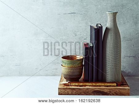 An arrangement of rustic ceramic decorations with  black notebooks