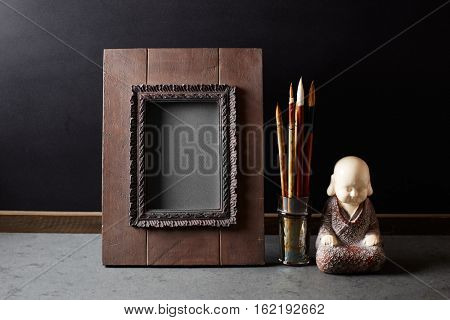 An arrangement of a rustic image frame, japanese calligraphy brushes and a meditation statuette