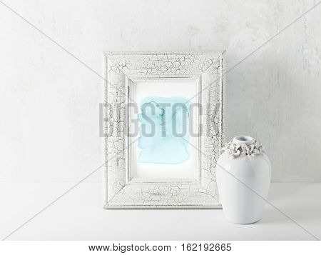An arrangement of an abstract watercolor picture and a vintage vase