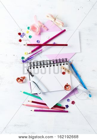 Assorted colorful art supplies on white wooden background