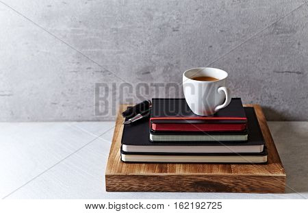 A cup of coffee on black notebooks