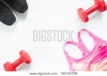 Flat lay of red dumbbells black sneakers and sport bra on white background. Sport wear Sport accessories top view