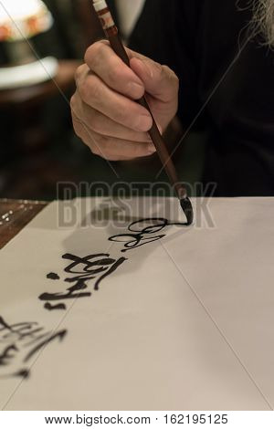 Calligraphy master drawing Chinese hieroglyphs in different styles with a brush