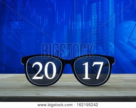 2017 text with eye glasses on wooden table over financial graph and city tower background Business vision concept