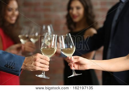 Female and male hands toasting with glasses of white wine, closeup