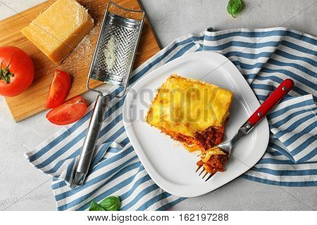 Plate with delicious lasagna and striped napkin on table