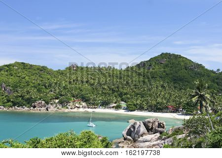white sailboat anchored in beautiful crystal bay surrounded by jugle clad hills near lamai on ko samui island in the gulf of thailand