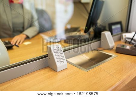 people, money, saving and finance concept - clerk at bank office or currency exchanger