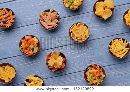 Different kinds of pasta in bowls on wooden background poster