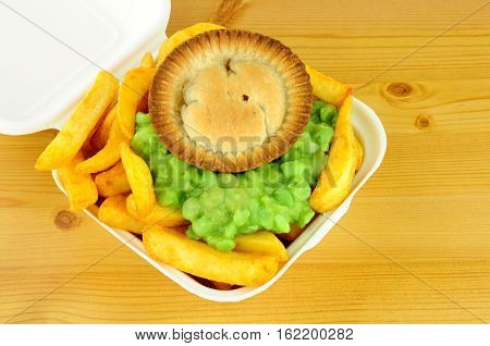 Meat pie and chips with mushy peas in a take away box