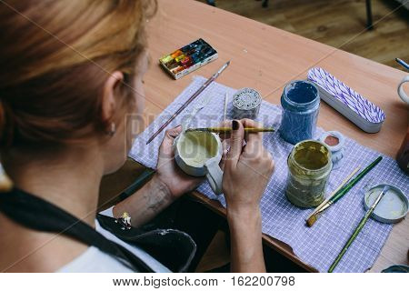 woman potter paints a clay cup. Woman working In her pottery studio