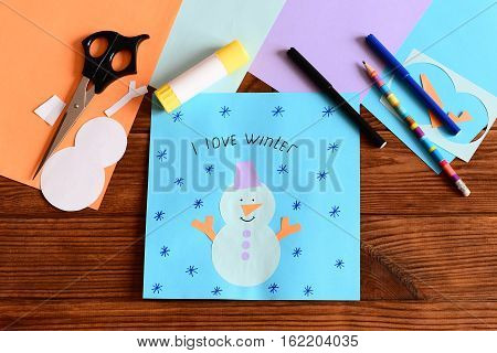 Paper snowman application card on wooden table. Tools and materials to create winter crafts. Simple craft for development kids fine motor skills and artistic taste, learning to use scissors and glue