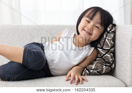 Happy Asian Chinese Little Girl Lying Down On The Sofa