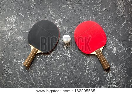 black racket for ping pong ball on gray background top view