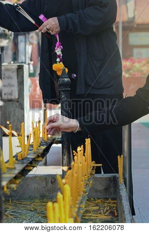 Placing A Lighted Candle On The Altar Of Buddha.