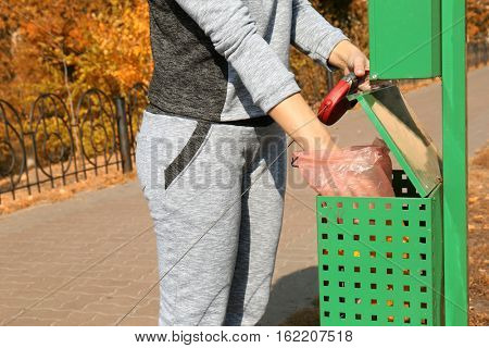 Woman throwing dog poo in container