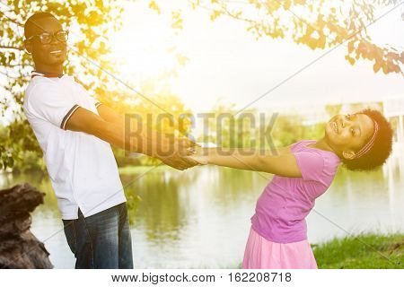 African American Father Playing And Holding Hands With Daughter In Outdoor Green Park