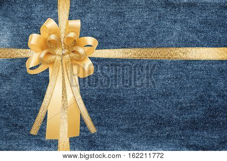 Golden ribbon with bow, on blue jeans texture, wrap gift box