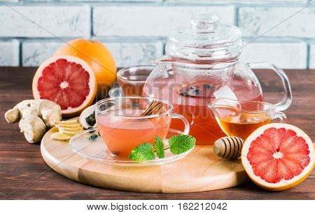 Grapefruit herbal tea with ginger and honey in a glass teapot and cup on wooden background