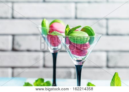 Red and green french cookies macaroons with a martini glass on a blue background.