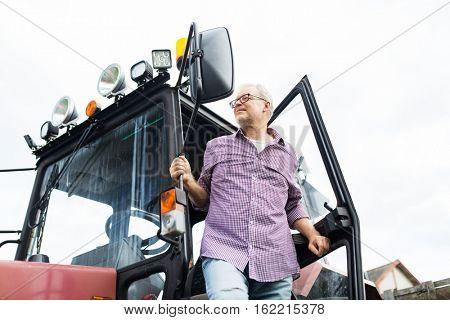 farming, agriculture and people concept - senior man or farmer getting out of tractor at farm