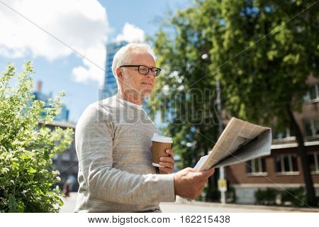 mass media, news and people concept - senior man reading newspaper and drinking coffee in city
