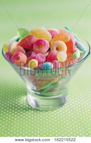 Glass bowl filled with brightly colored sweets (fruity jelly sweets), green dotted background.