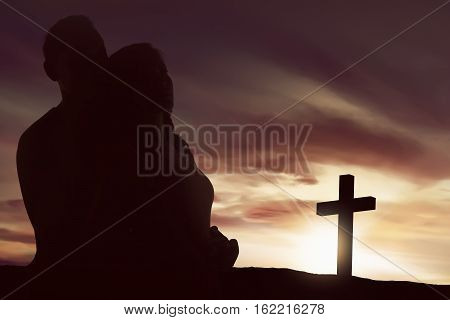 Silhouette asian couple looking christian cross shape over sunset sky