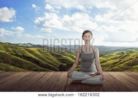 Young Asian Woman Doing Yoga Lotus Meditation On The Wooden Floor