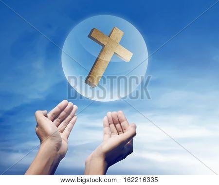 Hand Holding Christian Cross In Sphere