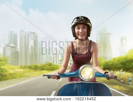 Beautiful asian women riding a blue scooter with helmet around a city street