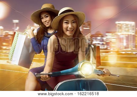 Attractive Two Asian Woman With Shopping Bag Riding The Scooter