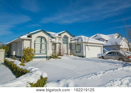 Big luxury house with parked car on driveway and front yard in snow. Residential house on winter sunny day