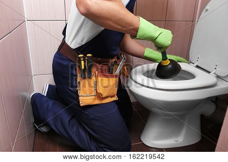 Plumber repairing toilet with hand plunger, closeup