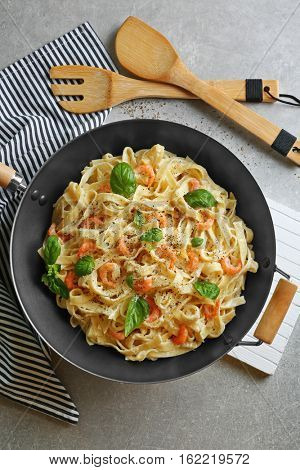 Pan with tasty alfredo pasta, kitchen board, napkin, spoon and fork on grey table