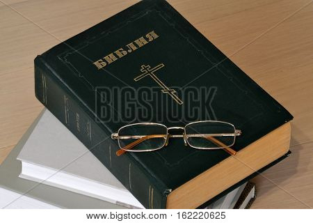 Closed Bible is dark green in color and points. Russian