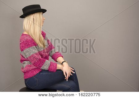Blonde girl in hat, striped sweater and jeans on grey background
