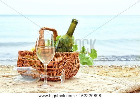 Glasses, basket with bottle and fresh grapes on beach