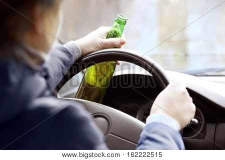 Woman holding bottle of beer while driving car, closeup. Don't drink and drive concept