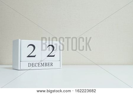 Closeup white wooden calendar with black 22 december word on blurred white wood desk and cream color wallpaper in room textured background with copy space selective focus at the calendar