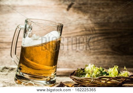 Beer mug stands on wooden table next to hop in basket