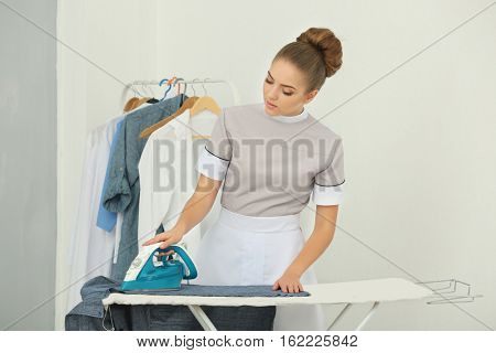 Chambermaid ironing clothes in a staff room