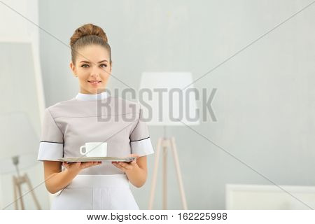 Hotel service concept. Chambermaid holding tray with cup of coffee