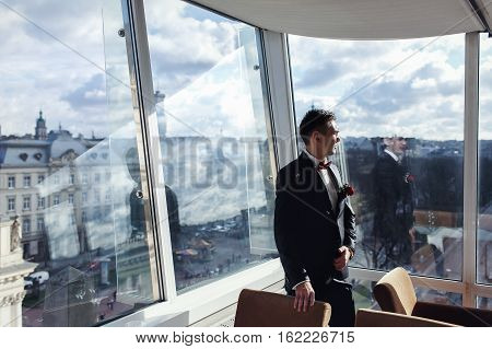 Elegant fiance stands before the panoramic windows