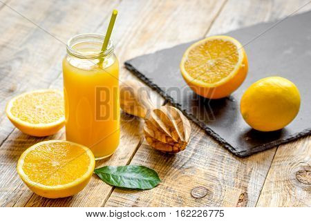 freshly squeezed orange juice in glass bottle on wooden background close up