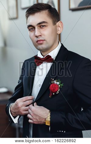 Confident Young Man In Tuxedo With Bow Tie Posing At Camera  Holding His Blazer