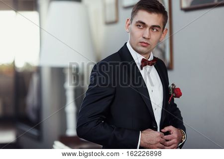 Confident young man in tuxedo with bow tie and boutonniere posing at camera holding his blazer