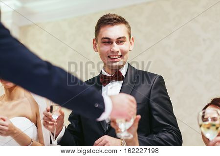 Fiance Smiles While Drinking To The Guests