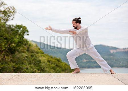 Kickboxer or muay thai fighter Man in white kimono training karate or Wushu on mountain background.